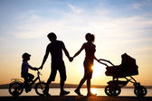 Happy family walking on sunset — Stok fotoğraf