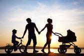Sunset bulvarında yürürken mutlu bir aile — Stok fotoğraf