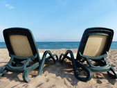 Two empty beach chairs on sea beach — Stok fotoğraf