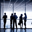 Several silhouettes of businesspeople interacting background business center — Stock Photo #28195903