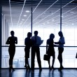 Several silhouettes of businesspeople interacting background business center — Stock Photo