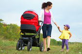 Mother with little daughter and pram — Stock Photo