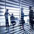 Silhouettes of business people through the blinds — Stock Photo