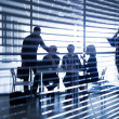 Silhouettes of business people through the blinds — Stock Photo #30730939