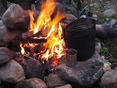 Tourist fire with a kettle and a mug — Stock Photo