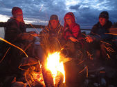 Tourists are heated at a fire at night — Stock Photo