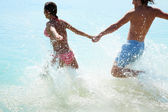 Couple in love runs into the sea — Stock Photo