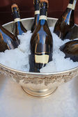 Wine bottles in cold ice bucket — Stock Photo