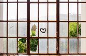 Heart painted on broken windows — Stock Photo