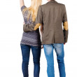 Back view of young couple pointing at wall. — Stock Photo #13755080