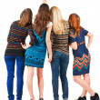 Back view of group beautiful women pointing at wall. - Stok fotoraf