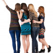 Back view of group beautiful women pointing at wall. — Стоковая фотография