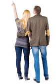 Back view of young couple pointing at wall. — Stock Photo