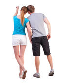 Back view of young couple pointing at wall — Stock Photo