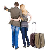Back view of traveling young couple with suitcas pointing — Stock Photo