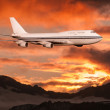Passenger airplane in the clouds at sunset or dawn. — Stock Photo #28197295
