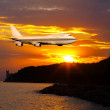 Passenger airplane in the clouds at sunset or dawn. — Stock Photo
