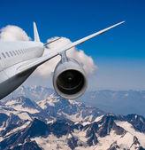 Samolot leciał nad ośnieżonymi szczytami. — Zdjęcie stockowe