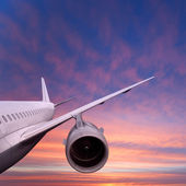 Plane is flying at sunset — Stock Photo