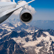 Plane flying over the snow-capped mountains. — Stock Photo
