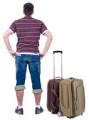 Back view of traveling man with suitcase looking up. — Stock Photo