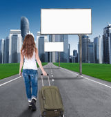 Woman walking on the road to the city, in front of an empty Bill — Stock Photo