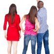 Back view of three friends. pointing man and two women looking. — Stock Photo