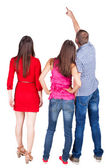 Back view of three friends. pointing man and two women looking. — Foto de Stock