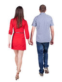 Back view going couple. walking friendly girl and guy holding ha — Stock Photo