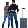 Young traveling couple with suitcas looks where that — Stock Photo #31926305