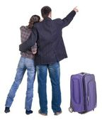 Traveling young couple with suitcas pointing at wall. Back view — Stock Photo