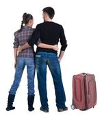 Young traveling couple with suitcas looks where that — Stock Photo