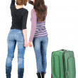 Two women traveling with suitcase and pointing at wall. — Stok fotoğraf