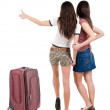 Two young  women friends traveling with suitcas and showing thum — Stock Photo