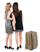 Two businesswoman traveling with suitcase and looking at wall. — Stock Photo
