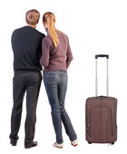 Back view of young couple traveling with suitcase. — Stock Photo