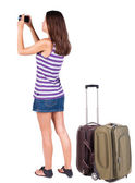 Back view of woman photographing traveling with suitcase. — Stock Photo