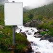 Billboard for advertising mounted next to a mountain stream — Stock Photo