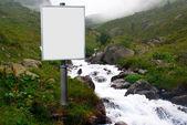 Reclamebord voor advertenties naast een bergbeek gemonteerd — Stockfoto