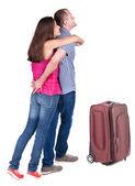Rückansicht des jungen paares reisen mit koffer. — Stockfoto