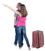 Young couple traveling with suitcas and pointing at wal Back vie — Stock Photo