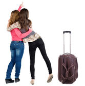 Back view of two young woman traveling with suitcase pointing — Stock Photo
