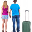 Back view of young embracing couple traveling with suitcase — Stock Photo