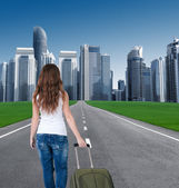 Rear view of a girl with a suitcase entering the city. — Stock Photo