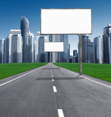 Road into town with established billboards — Stock Photo