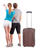 Young couple traveling with suitcase and pointing at wall — Stock Photo