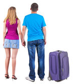 Back view of young couple traveling with suitcase — Stock Photo