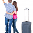 Stock Photo: Young couple traveling with suitcas and pointing at wall
