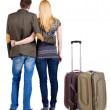 Back view of young couple traveling with suitcase. — Stockfoto #39359409