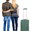 Back view of young couple traveling with suitcase. — Stockfoto #39359411